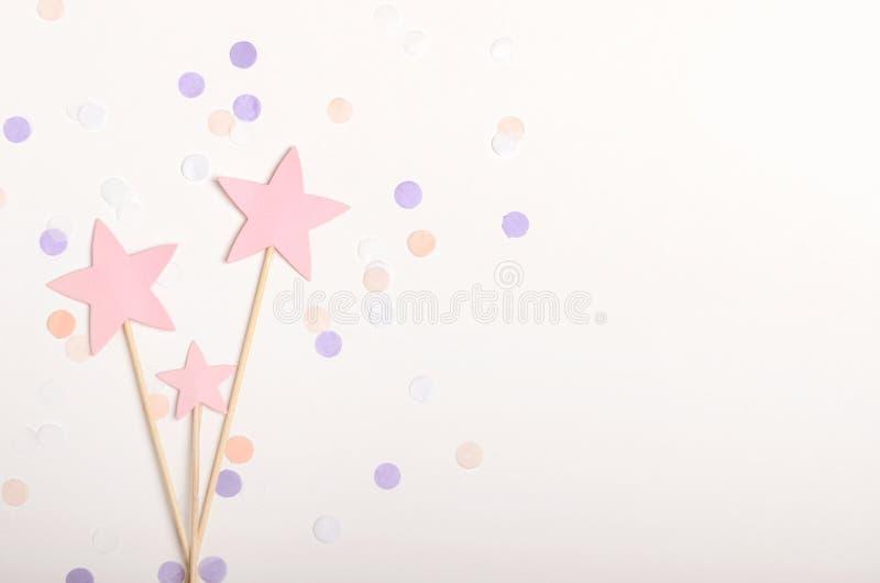 Estrelas cor-de-rosa na cobertura da vara no fundo branco com confetes, cores pastel O feriado das crianças, ano novo Vista super fotos de stock royalty free