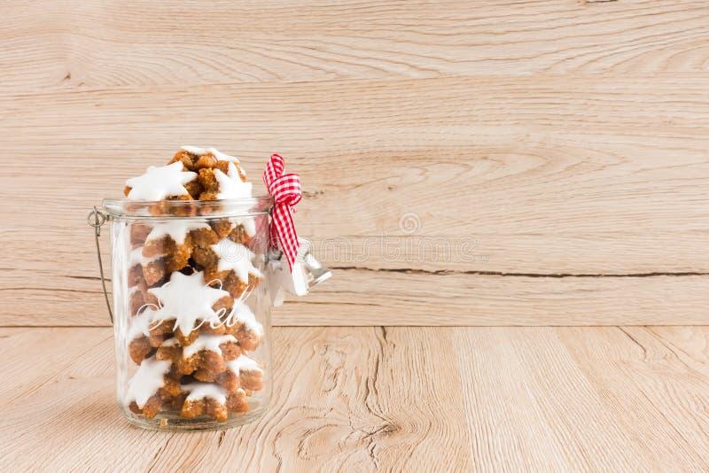 Estrelas da canela, Zimtsterne, cookies do Natal no frasco de vidro de Decoated fotografia de stock