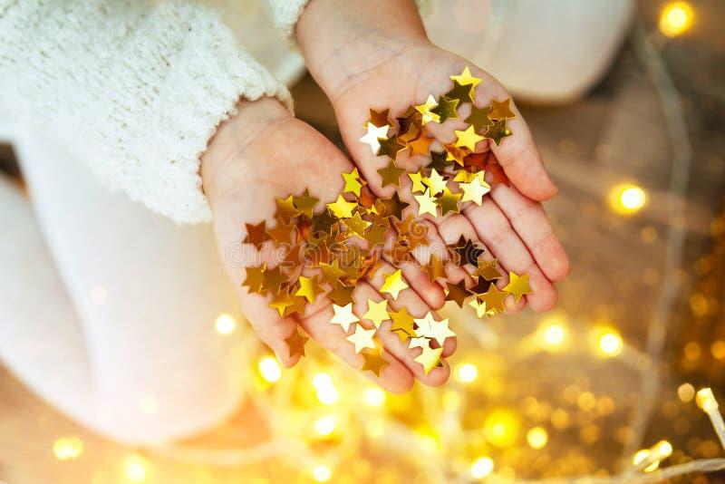 Estrelas douradas efervescentes nas mãos e nas palmas do ` s da criança imagens de stock royalty free
