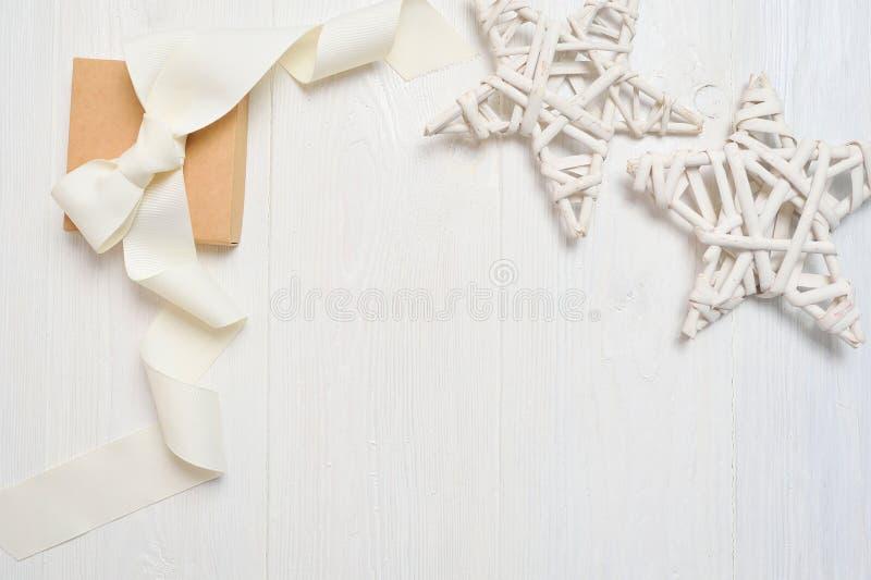 Estrelas e caixa da decoração do Natal com a curva branca que encontra-se na mesa de madeira branca Fundo abstrato do Natal Model imagem de stock royalty free