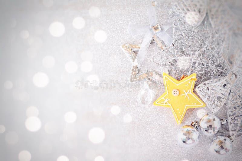 Estrella amarilla y ornamentos de plata brillantes en bokeh abstracto brillante del fondo imagen de archivo libre de regalías