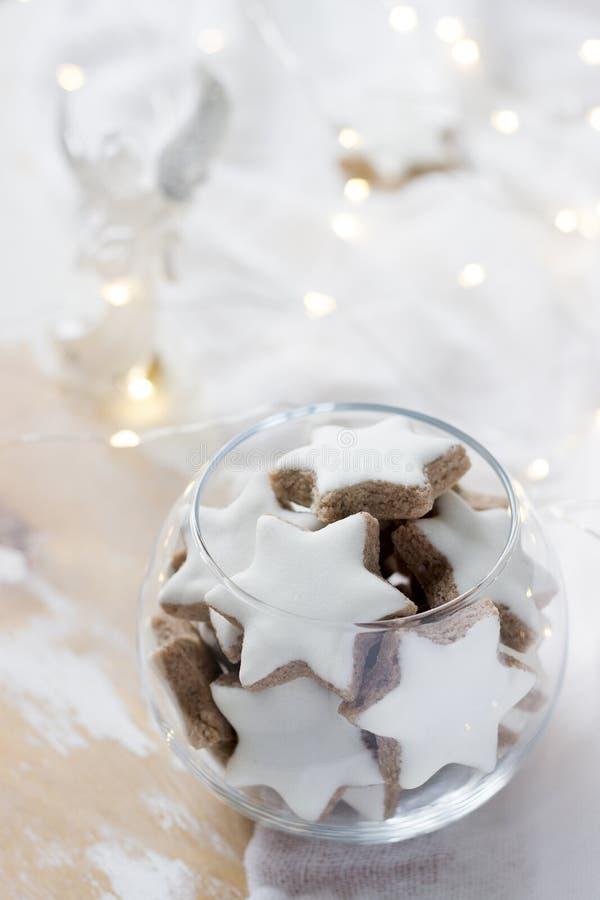 Estrella del canela de las galletas en un florero de cristal en un fondo blanco adornado con una estatuilla de un ángel y de una  imágenes de archivo libres de regalías