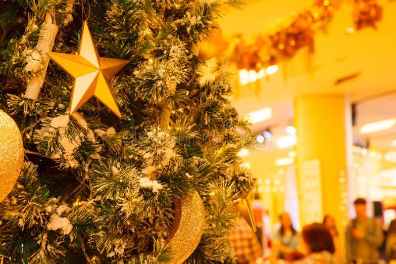 Estrella del oro, creciente y fondo colgantes de las chucherías de la bola que brillan con el árbol de navidad nevoso adornado de fotos de archivo libres de regalías