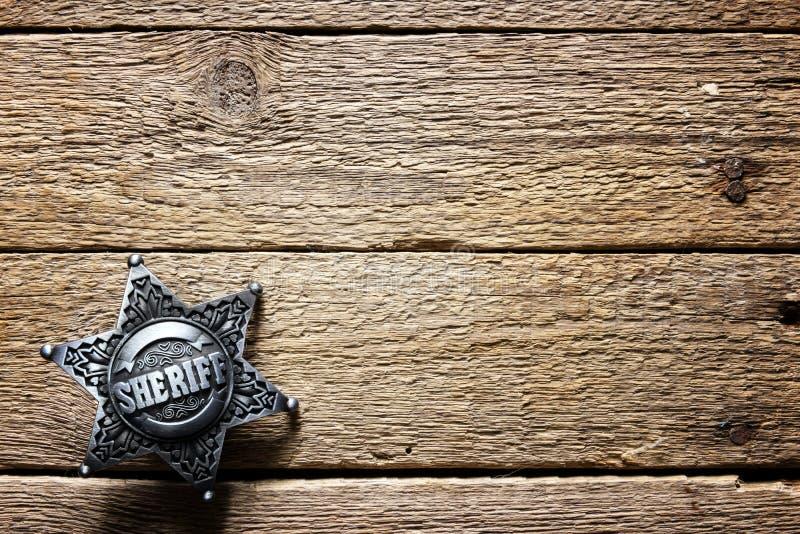 Estrella del sheriff en la tabla de madera imagen de archivo