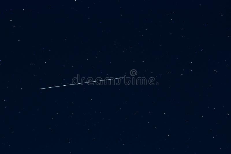 Estrella fugaz contra el cielo nocturno estrellado azul marino imagen de archivo libre de regalías