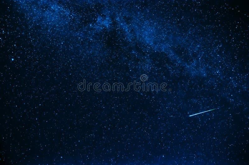 Estrella fugaz en fondo un cielo azul estrellado fotografía de archivo libre de regalías