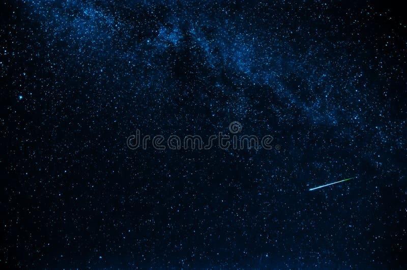 Estrella fugaz en fondo un cielo oscuro azul estrellado foto de archivo