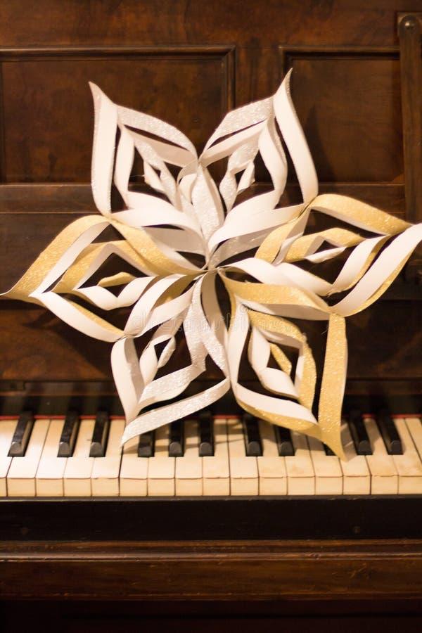 Estrella hecha a mano del papel de la Navidad en piano foto de archivo