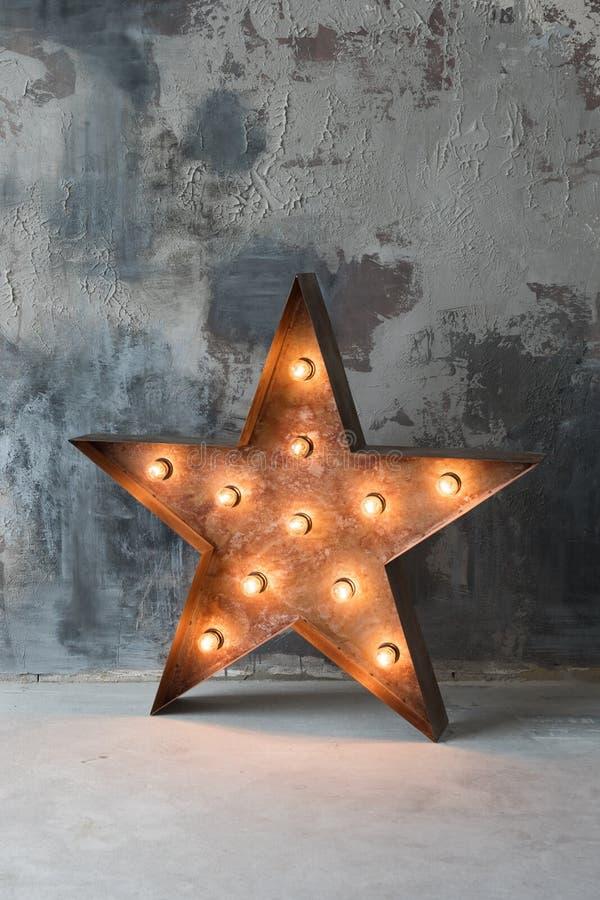 Estrella retra decorativa grande con las porciones de luces ardientes en fondo del hormigón del grunge Decoración hermosa, diseño foto de archivo