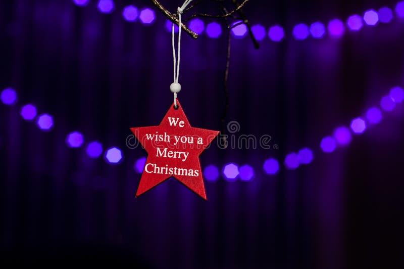 Estrella roja con lema: Le deseamos una Feliz Navidad imagen de archivo