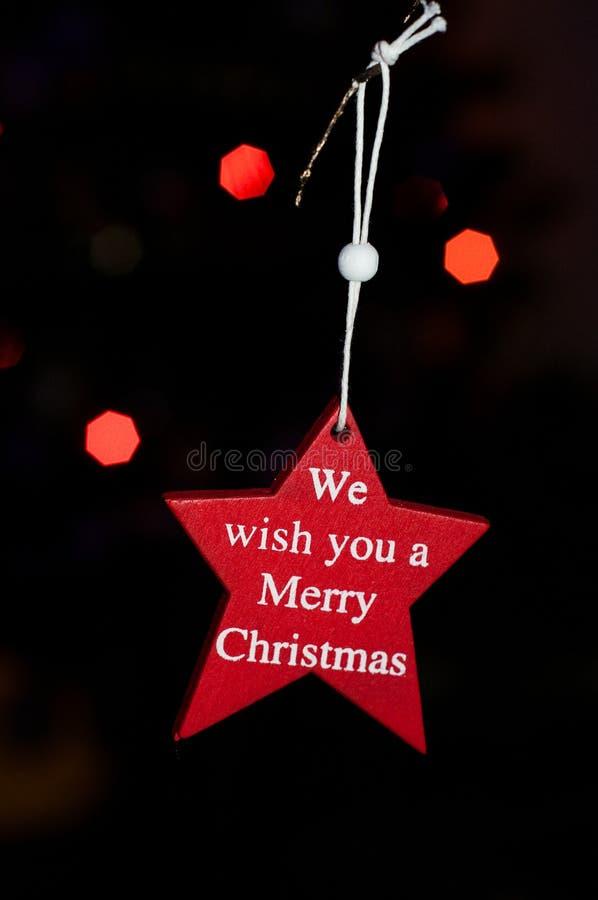 Estrella roja con lema: Le deseamos una Feliz Navidad imagen de archivo libre de regalías
