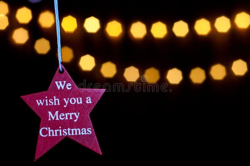 Estrella roja con lema: Le deseamos una Feliz Navidad fotos de archivo libres de regalías