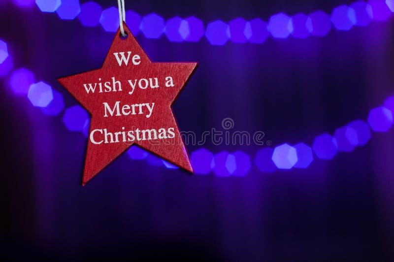 Estrella roja con lema: Le deseamos una Feliz Navidad foto de archivo libre de regalías