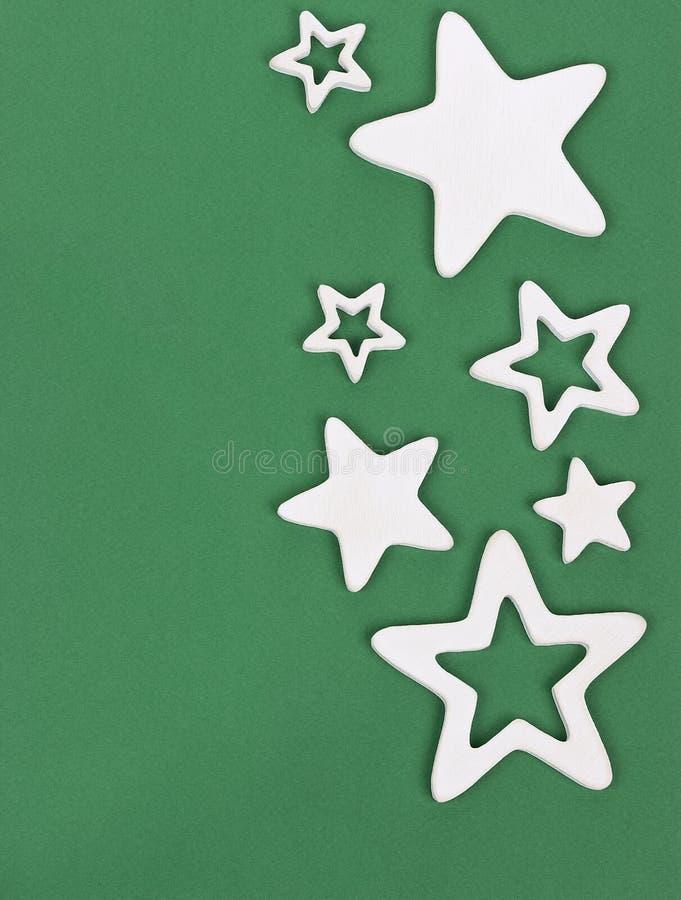 Estrellas de madera cinco-acentuadas blancas en la cartulina verde fotos de archivo
