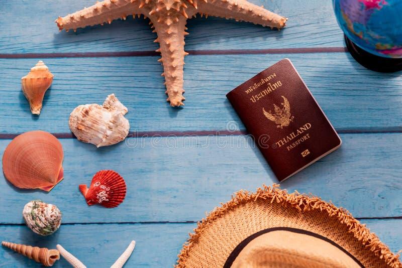 Estrellas de mar y conchas marinas cerca del sombrero, del globo del mundo y del pasaporte de Tailandia imágenes de archivo libres de regalías