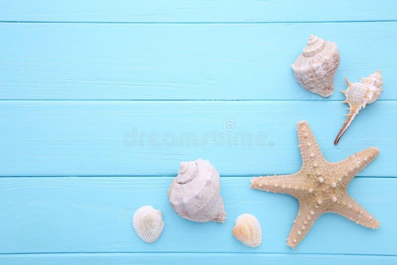 Estrellas de mar y conchas marinas en un fondo de madera azul Concepto del verano imagenes de archivo