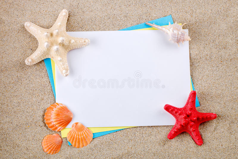 Estrellas de mar y conchas marinas que mienten en la arena en la postal fotografía de archivo