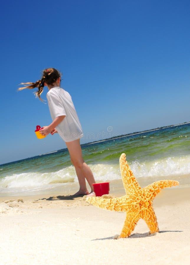 Estrellas de mar y muchacha en la playa imagen de archivo libre de regalías