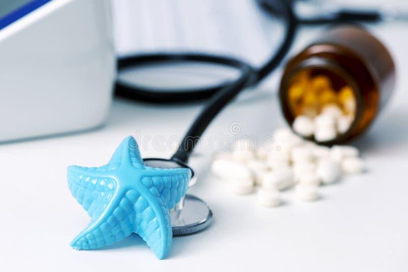 Estrellas de mar y píldoras en el escritorio de los doctores imágenes de archivo libres de regalías