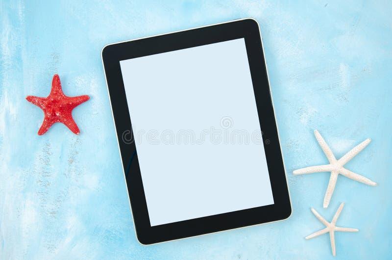 Estrellas de mar y PC puestas planas de la tableta en fondo azul en colores pastel Marco de la visi?n superior con el espacio de  imagen de archivo