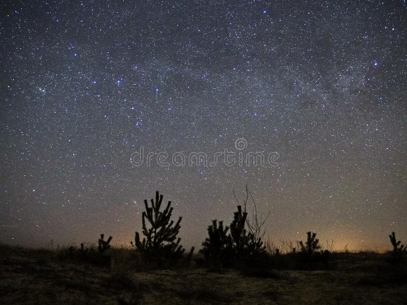 Estrellas del cielo nocturno y de la vía láctea, Cassiopeia y constelación del andromeda sobre el mar fotografía de archivo