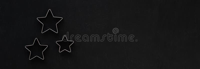 Estrellas del metal en fondo festivo negro Moldes que cuecen Cortadores de la galleta Endecha plana, visión superior foto de archivo