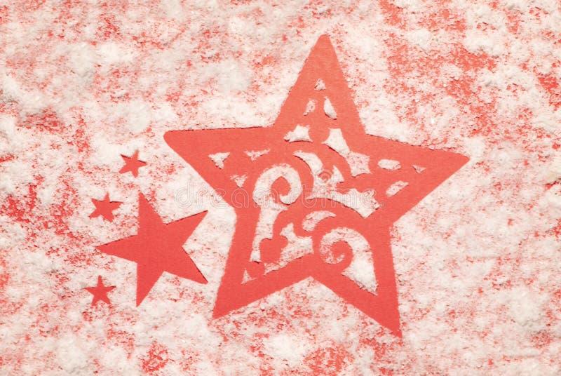 Estrellas en la nieve, fondo rojo foto de archivo