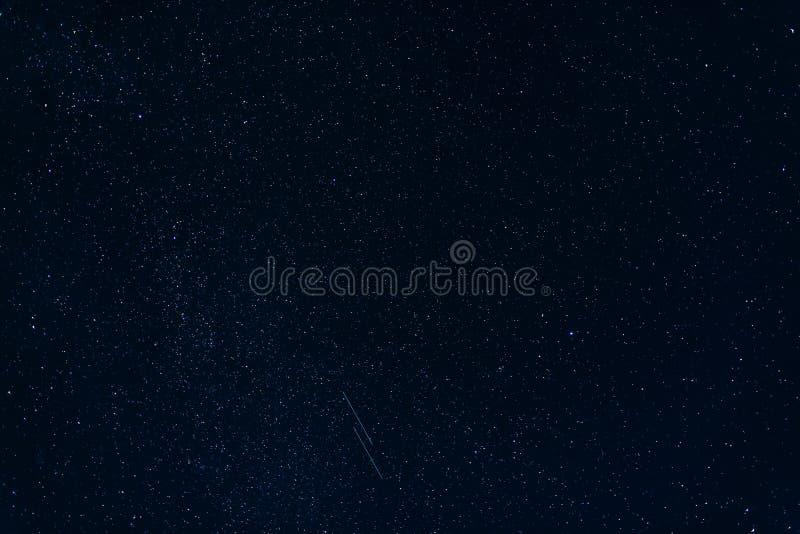 Estrellas fugaces contra el azul estrellado del cielo nocturno con la vía láctea fotografía de archivo