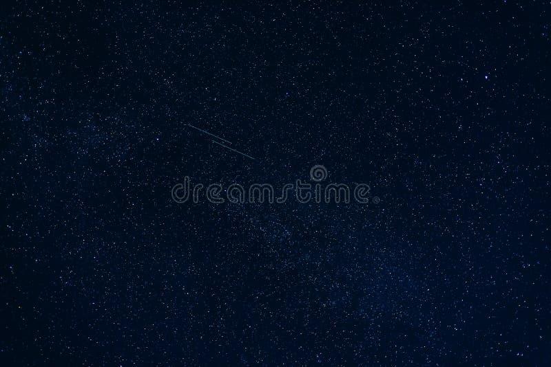 Estrellas fugaces en cielo nocturno azul marino estrellado fotos de archivo