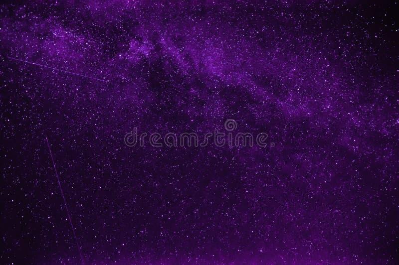 Estrellas fugaces en fondo un cielo nocturno púrpura imágenes de archivo libres de regalías