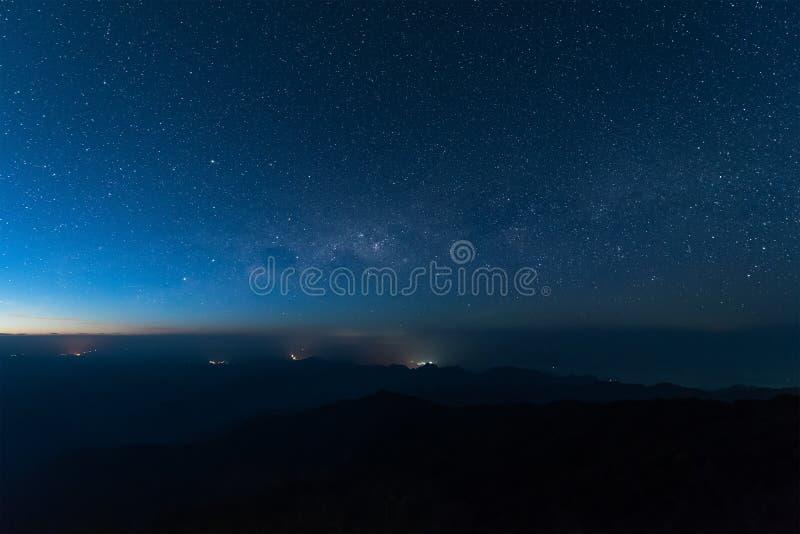 Estrellas iluminadas sobre la montaña oscura de la silueta antes de salida del sol fotos de archivo