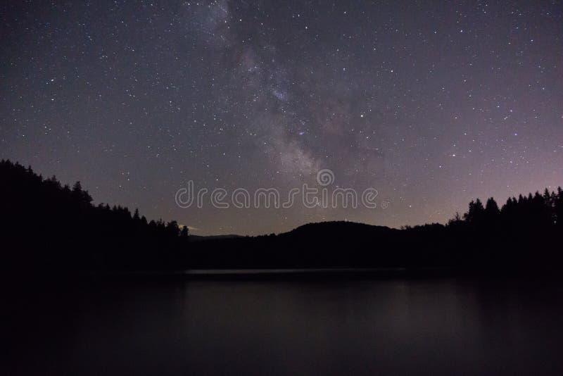 Estrellas púrpuras del cielo nocturno sobre el lago de la montaña Galaxia de la v?a l?ctea en noche estrellada del verano foto de archivo