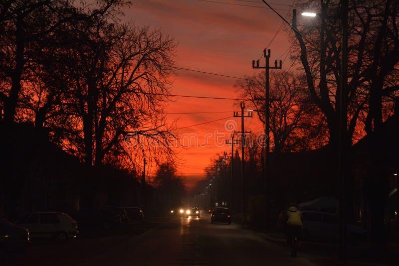 Estrema luce rossa nel cielo serale, in strada fotografia stock libera da diritti