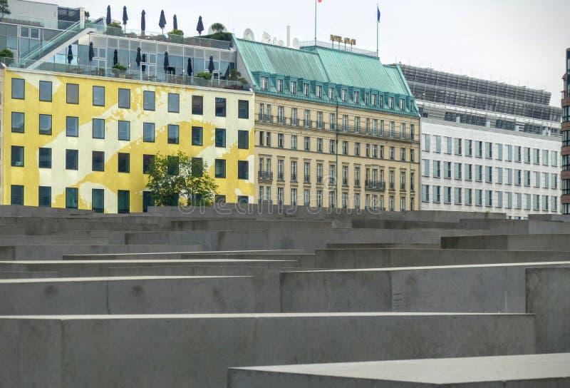 Estremità delle colonne del memoriale dell'olocausto con le costruzioni colorate a sinistra berlino germany immagini stock libere da diritti