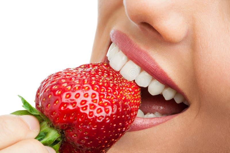 Estremo vicino su dei denti che mordono fragola. immagini stock