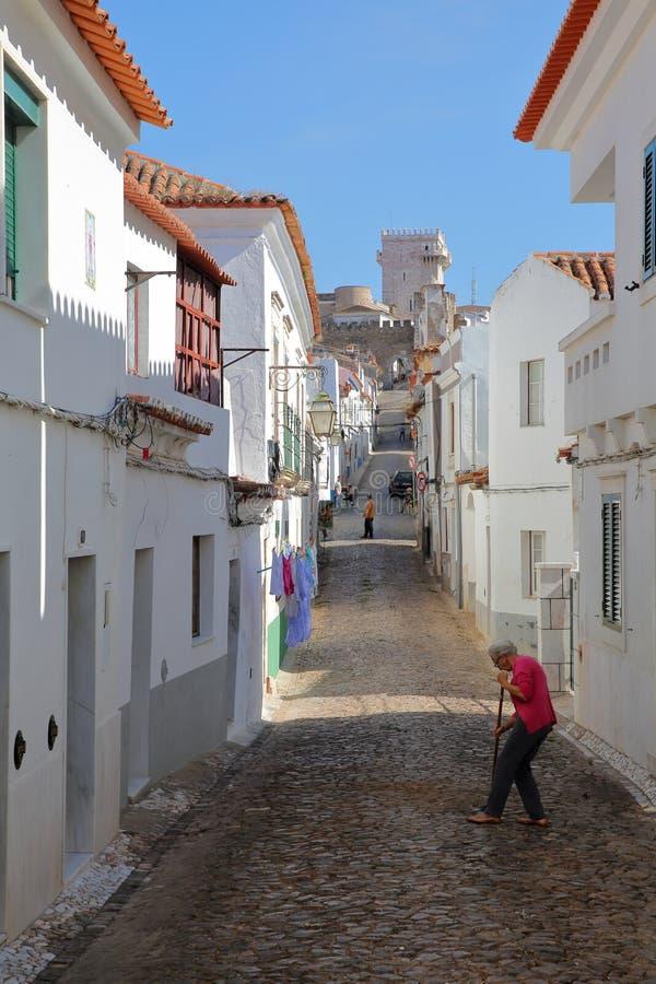 ESTREMOZ, PORTUGAL - OKTOBER 10, 2016: Typisch cobbled straat met de Toren van de Drie Kronen Torre das Tres Coroas in stock afbeelding