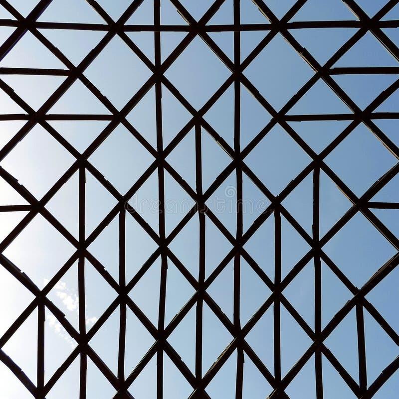 Estructura inusual geométrica con las barras de madera cruzadas imagenes de archivo
