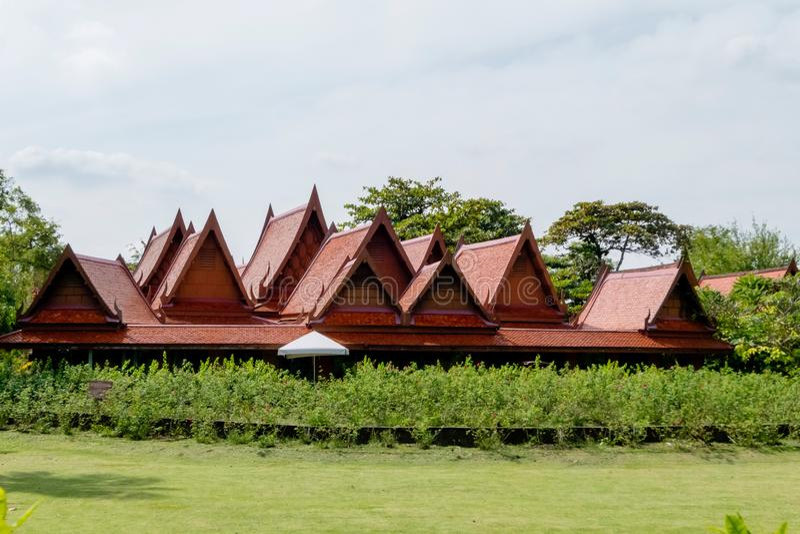 Estrutura de telhado da casa tailandesa velha grande e bonita do estilo com a jarda verde do beira-rio de Sampran mais quente Nak foto de stock
