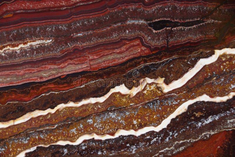 A estrutura do ônix, uma cor vermelha brilhante com raias escuras e as ondas, são chamadas Ônix Fantastico imagem de stock royalty free
