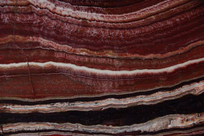 A estrutura do ônix, uma cor vermelha brilhante com veias finas e as ondas, são chamadas Onice Fantastico fotografia de stock
