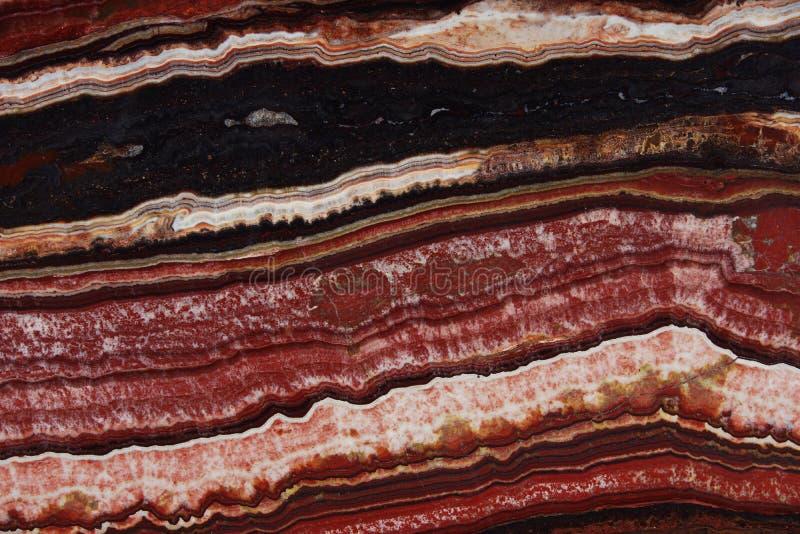 A estrutura do ônix, uma cor vermelha brilhante com veias finas e as ondas, são chamadas Onice Fantastico fotos de stock royalty free