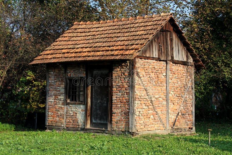 Estrutura velha do armazenamento do tijolo vermelho do quintal com as portas de madeira dilapidadas e janela cercada com grama ve fotos de stock
