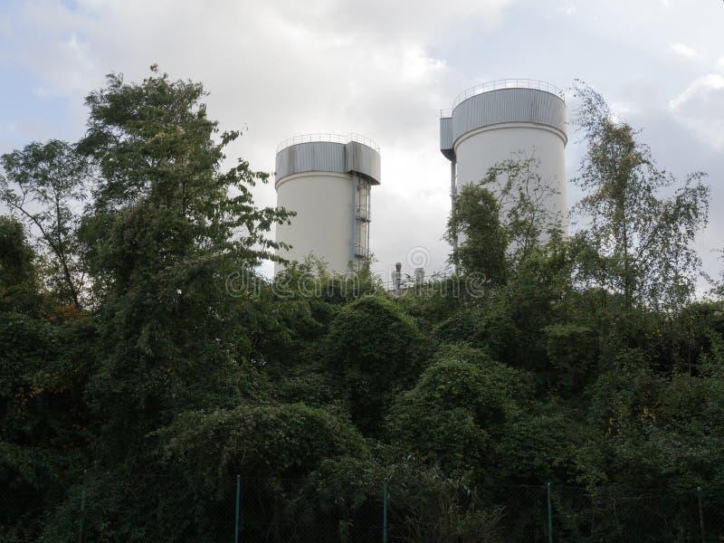 Estruturas industriais entre arvoredos verdes foto de stock