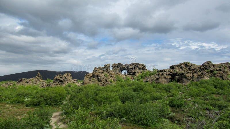 Estruturas pretas dramáticas da rocha da lava, formações vulcânicas originais do fluxo e floresta islandêsa verde, área de Myvatn fotografia de stock royalty free