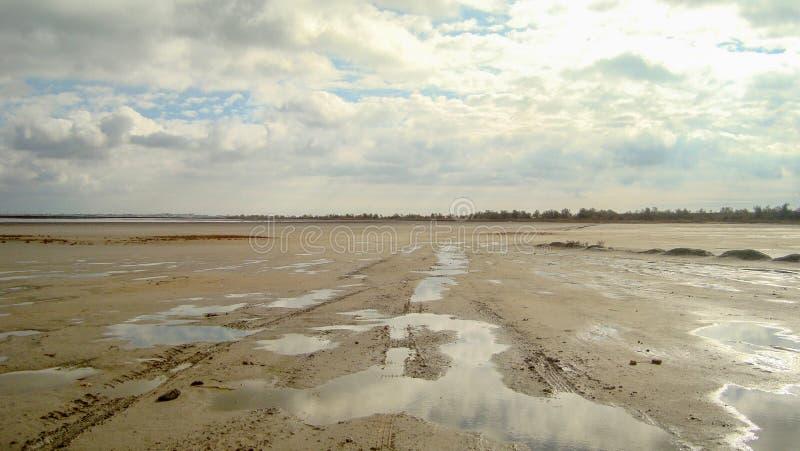 Estuario sabbioso inaridito sotto il cielo nuvoloso infinito fotografia stock