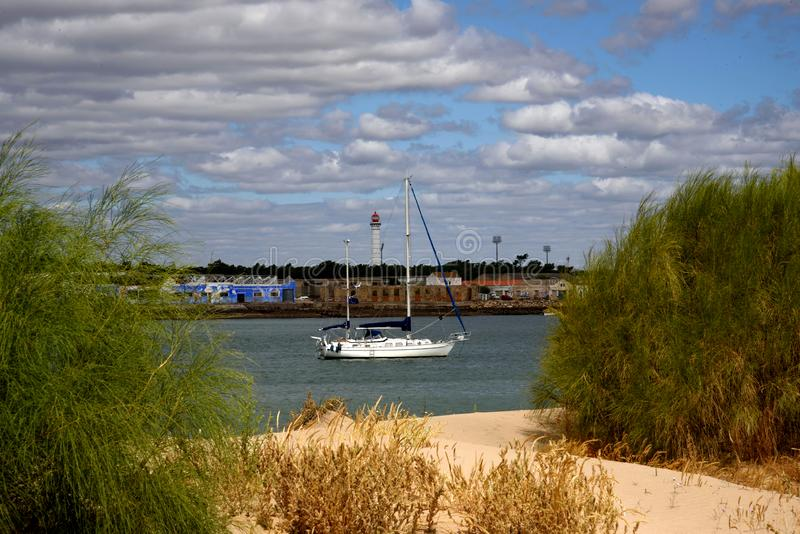 Estuary of Guadiana river. Sailing boat ancored in estuary of Guadiana river  separating  Andalucia Spain from Algarve Portugal stock image