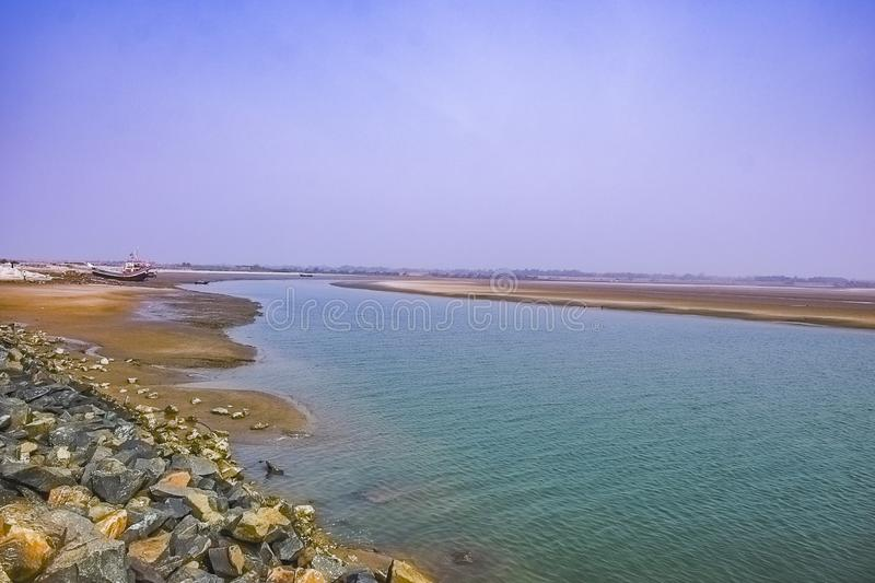 Estuary, mouth of a river, outlet with a boat at the east cost India at the Sunrise in a clear morning Spring time. February 2018 stock photos