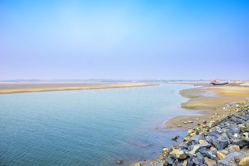 Estuary, mouth of a river, outlet with a boat at the east cost India at the Sunrise in a clear morning Spring time. royalty free stock photography