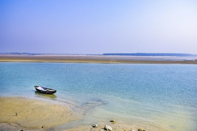 Estuary, mouth of a river, outlet with a boat at the east cost India at the Sunrise in a clear morning Spring time. February 2018 royalty free stock images