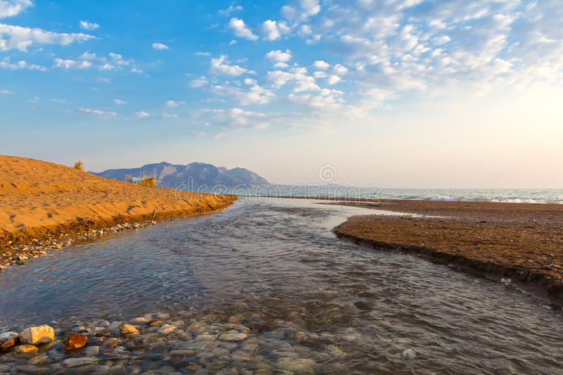 Estuary of a small river on a sandy beach, Greece. Estuary of a small river full of reeds on a sandy beach. Neda river at western Peloponnese, Greece royalty free stock photography